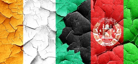 Ivory coast flag with afghanistan flag on a grunge cracked wall Stock Photo