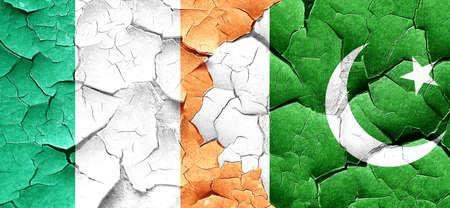bandera irlanda: Ireland flag with Pakistan flag on a grunge cracked wall