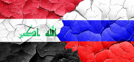 russia flag: Iraq flag with Russia flag on a grunge cracked wall