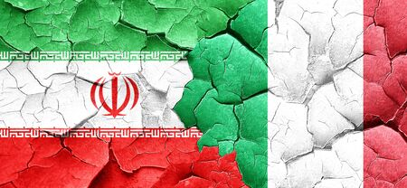 against: iran flag with Italy flag on a grunge cracked wall Stock Photo
