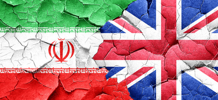 england politics: iran flag with Great Britain flag on a grunge cracked wall