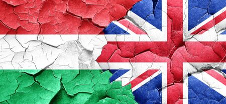 british culture: Hungary flag with Great Britain flag on a grunge cracked wall