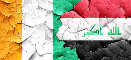 iraq conflict: Ivory coast flag with Iraq flag on a grunge cracked wall