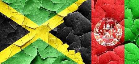 Jamaica flag with afghanistan flag on a grunge cracked wall
