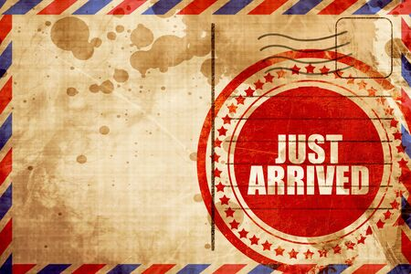 just arrived: just arrived, red grunge stamp on an airmail background