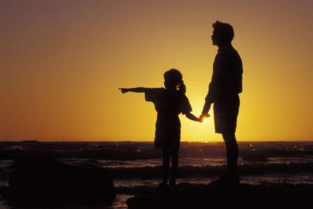 water's edge: Father and daughter standing on the beach at sunset