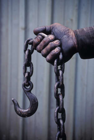 Workers hand holding a chain and hook
