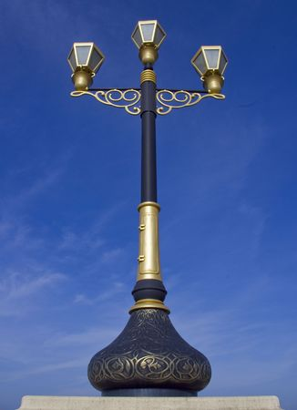 metal post: Artistic and Decorative Black and Gold Metal Post with three bulbs Stock Photo