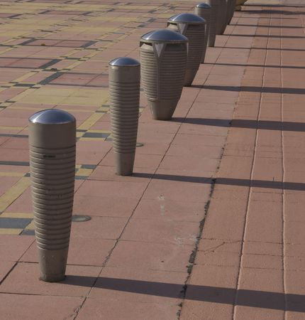bollards: Street Bollards - gray color, oval shape, groove cicle, pink tiles, long shadow  Stock Photo