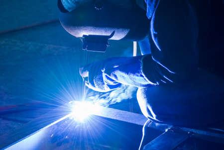 soldador: Soldador trabajando un trabajo de soldadura de metal con la máscara protectora y chispas para la construcción
