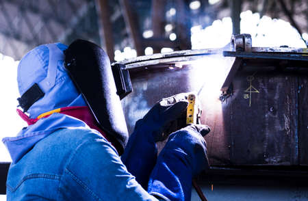 Welder working a welding metal work with protective mask and sparks for construction photo