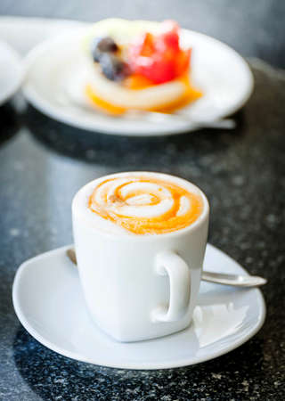 Cup of coffee with sweet fruit tart cake on disc photo