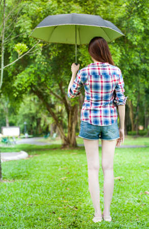 Portrait of beautiful young woman with umbrella in garden park photo