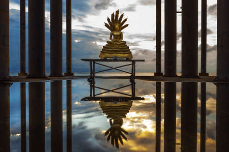 Buddha statue with reflection on water in the evening. photo