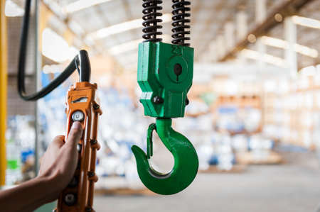 Green crane hook with some industrial valve on the background