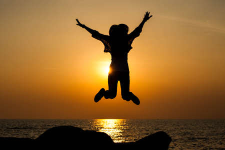 Successful woman jumping, dancing and having fun on sunset in beach. Freedom and happiness concept. Girl celebrating work out success.