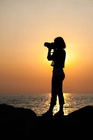 man woman silhouette: Silhouette woman photographer seascape at sunset Stock Photo