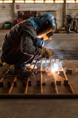 metal structure: Worker with protective mask welding metal structure Stock Photo