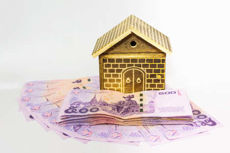 escrow: The house on pile of money. Concept of real estate.