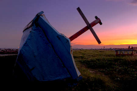 red cross red bird: The old fishing boat over a sunset or sunrise sky Stock Photo