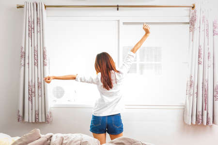 Back view portrait of young woman stretching her hands in morning at home