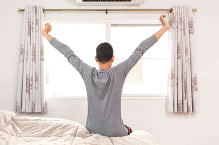 Cropped shot of a young man stretching in bed while waking up Imagens