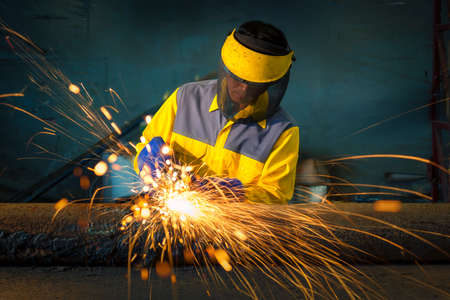The worker grinding metal in manufacturing plant, sparks flying on piping metal