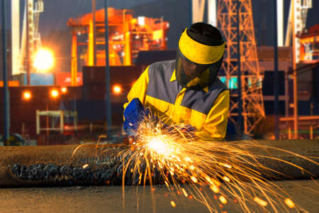 The worker grinding metal in manufacturing plant, sparks flying on piping metal?