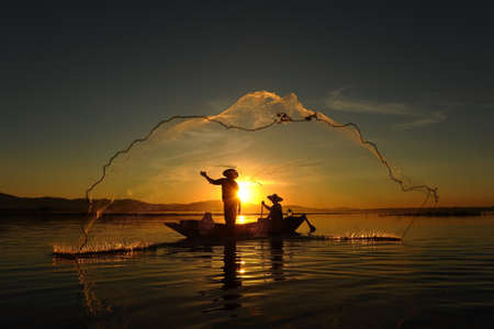 Fisherman of asian people at Lake in action when fishing during sunrise