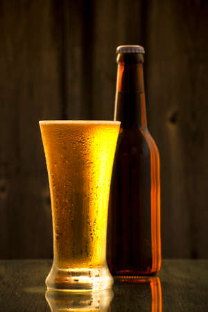 A bottle of cold draft beer with a glass Imagens