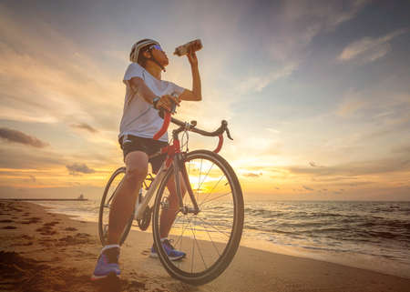Cycling outdoors against sunset Imagens