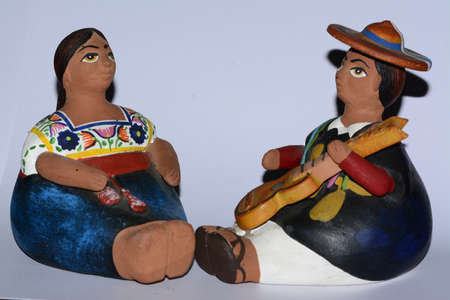 Mexican ethnic clay dolls on white background