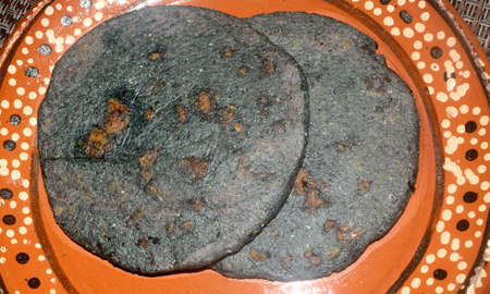 Mexican gordita made with blue corn and filled with pork