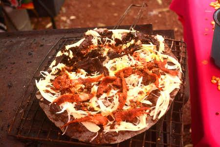 ストーブまたはメキシコ、オアハカ チーズとぎくしゃくした牛肉、豆おいしい巨大なトルティーヤの anafre で調理されている Tlayuda 写真素材