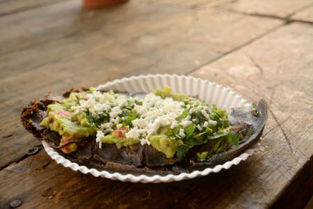 Mexican tlacoyos, a dish made with blue corn and filled with fried beans or broad beans, similar to mexican gordita, with guacamole, spicy sauce, coriander and cheese at the top