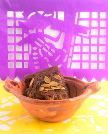 Mexican traditional pumpkin sweet made with piloncillo and cinammon on a clay pot, known as calabaza en tacha with ornamental papel picado