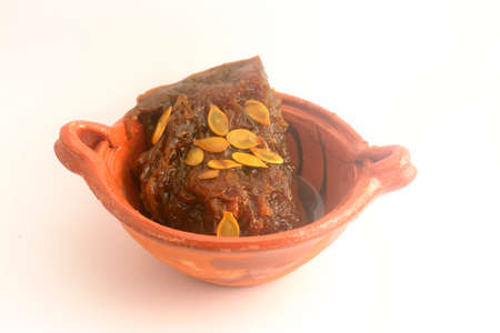 Mexican traditional pumpkin sweet made with piloncillo and cinammon on a clay pot, known as calabaza en tacha