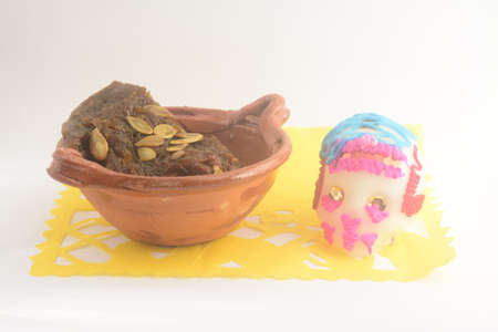 Mexican traditional pumpkin sweet made with piloncillo and cinammon on a clay pot, known as calabaza en tacha with ornamental papel picado and traditional sugar skull