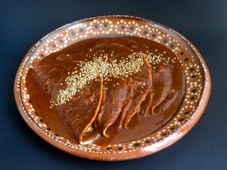 Deliciosas enchiladas mexicanas, tacos de pollo o pavo con salsa de mole y semillas de sésamo para fiestas tradicionales Foto de archivo