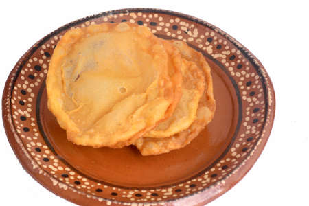 Mexican traditional fried dough buñuelo with piloncillo syrup on clay dish