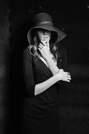 velvet dress: Mysterious young woman in black dress and straw wide-brimmed hat  Black-white photo