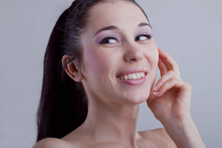 Portrait of young beautiful laughing woman touching skin on white background  Enjoment of life  Emotions  Smile  photo