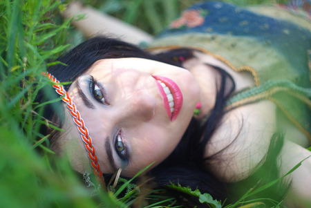 bohemian: Portrait of beautiful young woman of hippie posing outdoor  Enjoy nature  Healthy smiling  Girl in green grass  Fashion model  Bohemian style Stock Photo