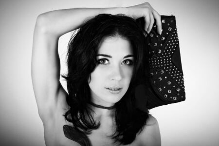 clutches: Portrait of beautiful young woman with natural makeup holding  black clutch with rivets  Black white photo
