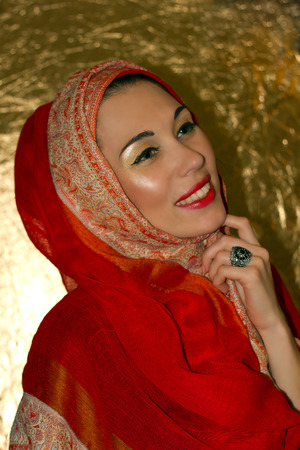 engaging: Portrait of laughing beautiful arabic young woman with gold makeup. Red clothes. Shawl with ornament. Gold ring with precious jewels. Shiny skin texture. Engaging smile.