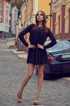 Young beautiful woman standing on the ancient street of old town wearing black skirt and sweater photo