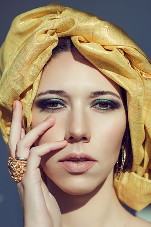 cryptic: Close up fashion portrait of cryptic beautiful young woman in yellow turban.