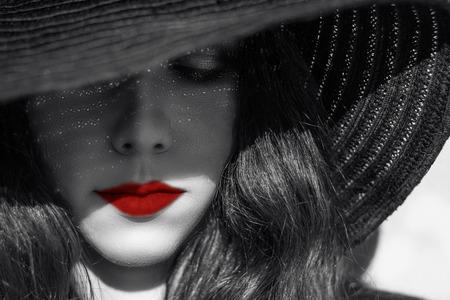 Portret van mysterieuze mooie jonge vrouw met een prachtige huid textuur in zwarte hoed. Stockfoto