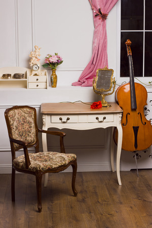 Modern antique interior of living room. White nightstand with photo frame and red flower. Chair with upholstery. Violoncello. Shelf with carved  vintage boxes, clock with angels, vase with flowers.