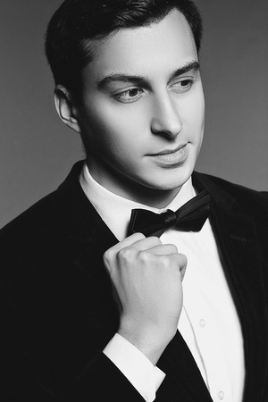 manhood: Close-up portrait of handsome elegant young man in black suit, bow tie and shirt on white background. Fashion model studio shooting. Manhood and sexuality. Black white photo. Luxury style.
